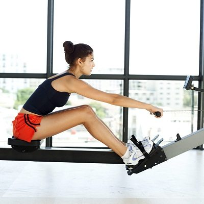 Young Woman Exercising on a Rowing Machine